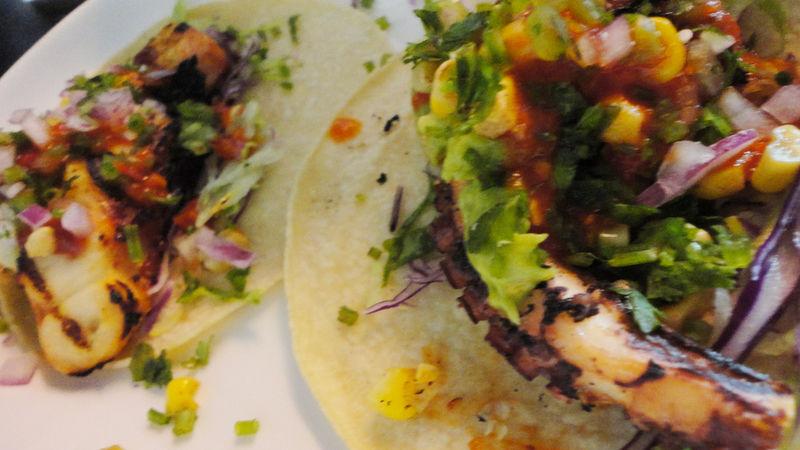 Pulpo asado en tacos con salsa, papas y cebollitas encurtidas
