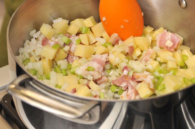 Pelar las papas y cortar en cubos pequeños. Picar finamente la cebolla, el ajo y el apio. Cortar el tocino en cuadros pequeños. Dorar todo en una olla honda con aceite de oliva durante 5 a 8 minutos.