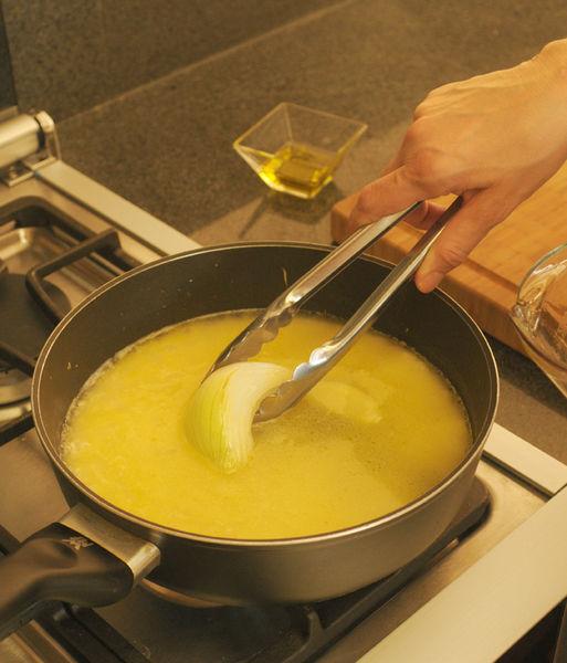 Agregar el caldo de pollo, retirar la cebolla y revisar la sazón de sal. Cuando suelte el primer hervor bajar la lumbre y cocer tapado a fuego lento durante 10 o 15 minutos, hasta que se consuma el líquido.
