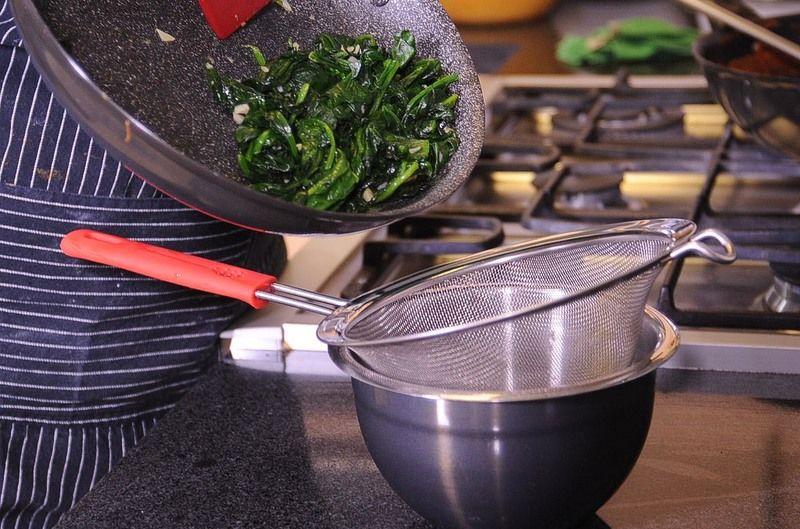 Colocar las espinacas en un colador y presionar para escurrir la mayor cantidad de líquido. Pre- calentar el horno a 350 ° F (175°C).
