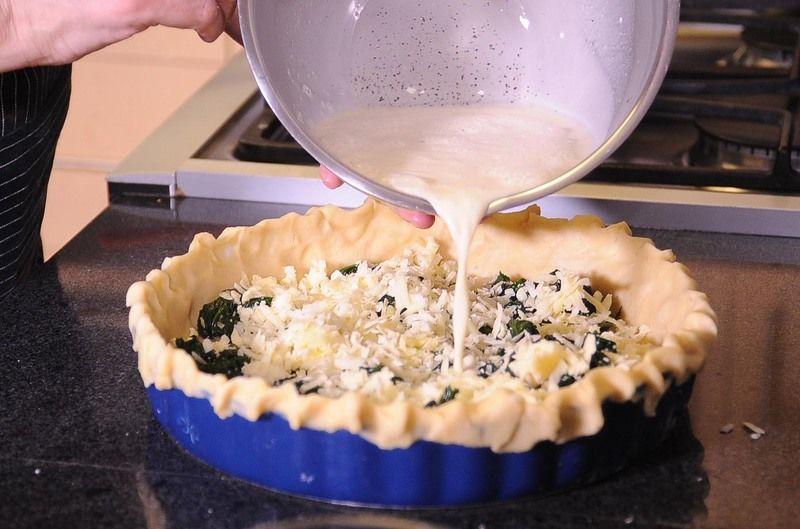 Colocar las espinacas y el queso gruyere bien esparcidos sobre la masa base en el molde para pay. Agregar la mezcla de huevo batido.