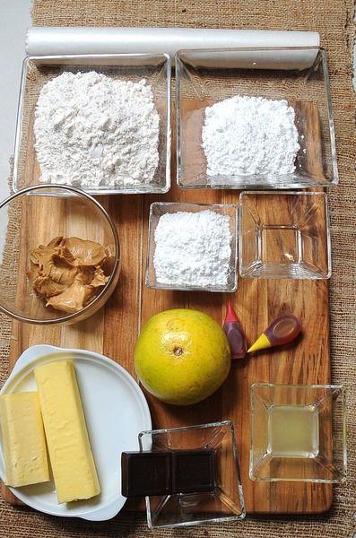 Ingredientes para las galletas: 150 gramos de mantequilla sin sal 1/3 taza de azúcar glass (pulverizada) 1 pieza de naranja 1 2/3 tazas de harina de trigo papel encerado al gusto Ingredientes para relleno: 30 gramos de chocolate amargo para repostería 1/2 taza de mantequilla de cacahuate Ingredientes para glaseado: 1/2 taza de azúcar glass (pulverizada) 1 cucharada de jugo de naranja 1 cucharita de esencia de naranja colorante rojo vegetal al gusto colorante amarillo vegetal al gusto
