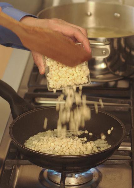 Asar el chile poblano, quitar la piel, desvenar y cortar en rajas. Picar la cebolla y el ajo finamente. Acitronar un poco de la cebolla y el ajo en una sartén abierta con aceite de oliva hasta que la cebolla se torne transparente. Agregar el elote y cocer de 5 a 8 minutos hasta que el elote esté suave.