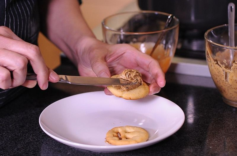 Colocar un poco de la mantequilla sobre la galleta sin cara, y colocar encima la otra galleta con cara, presionando para unirlas como si fuera un sándwich.