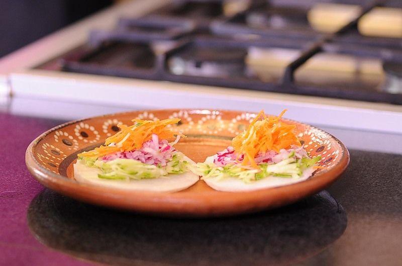 Colocar las rebanadas de jícama en un plato y colocar encima un poco de calabacita rallada, rábano rallado, zanahoria rallada.