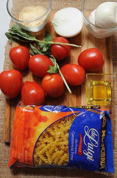 500 gramos de fusilli De Luigi alta proteína 8 piezas de jitomate guaje 300 gramos de queso mozzarella 3 cucharadas de aceite de oliva 1/2 pieza de cebolla blanca 1/2 taza de queso parmesano sal al gusto pimienta al gusto 2 ramas de albahaca fresca