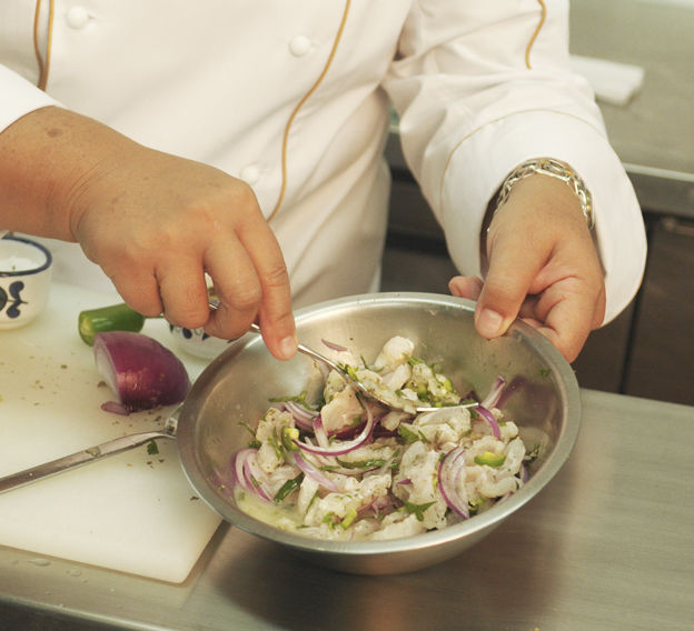 Picar finamente el chile serrano y el perejil. Cortar la cebolla en rebanadas delgadas. Agregar los ingredientes picados al pescado. Sazonar con el orégano previamente tallado en las manos para que la temperatura de las manos logre extraer sus aceites naturales y su olor.