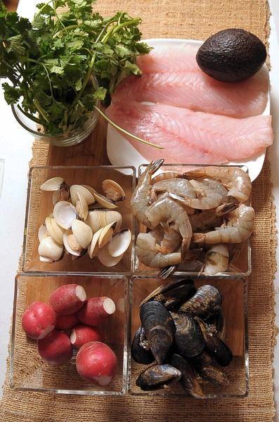 Ingredientes para toda la receta: 1/4 cucharita de comino molido 1/4 pieza de cebolla blanca 3 ramas de epazote 8 piezas de tomate verde (tomatillo) 1/4 cucharita de pimienta negra molida 1 diente de ajo 2 piezas de chile serrano 1 kilogramo de maíz pozolero precocido 1/2 manojo de perejil 1/2 manojo de cilantro 1 kilogramo de pescado blanco 500 gramos de camarón 40/50 300 gramos de mejillones 300 gramos de almeja blanca sal al gusto