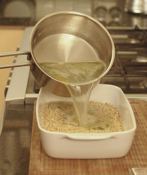 Colocar el arroz en una fuente para horno, agregar el agua caliente.