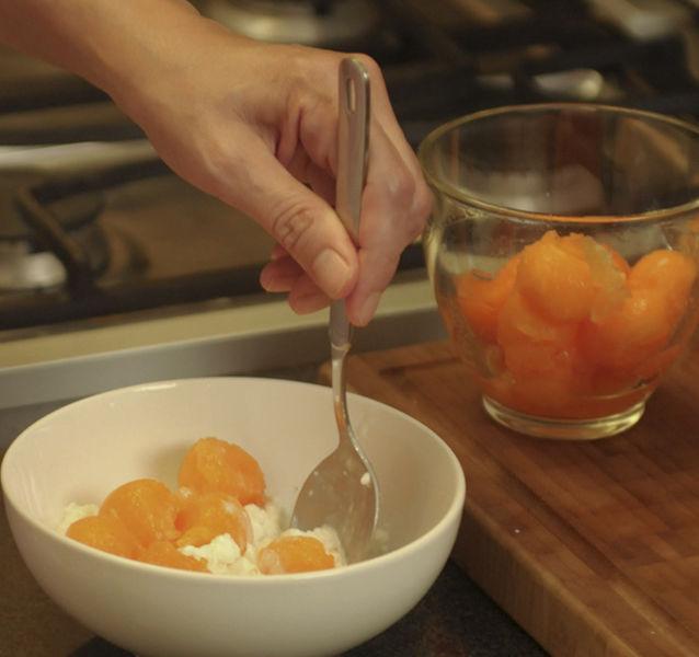 Servir la mitad del queso cottage en cada plato hondo. Agregar la mitad de las bolitas de melón a cada uno.