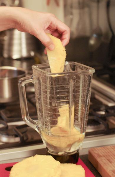 Pelar la piña con el cuchillo, cortar en rebanadas, retirar el centro fibroso de cada rebanada con un cuchillo. Cortar en cubos pequeños dos de las rebanadas, licuar el resto de la pulpa en la licuadora junto con jarabe de azúcar.