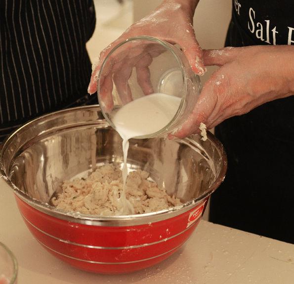 Añadir el tomillo, el romero y el perejil. Mezclar los ingredientes. Incorporar con las manos la mantequilla con el harina, frotando con los dedos un pedacito de mantequilla con harina a la vez. Agregar la leche, poco a poco, hasta que se forme una masa suave que no se pegue en las manos la cantidad de leche puede variar, si la masa está pegajosa, agregar un poco más de harina.