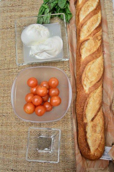 Ingredientes para toda la receta 2 piezas de queso burrata Nuevo 1 taza de jitomate cherry sal de mar al gusto pimienta negra molida al gusto aceite de oliva al gusto 1 pieza de baguette 1 manojo de albahaca fresca