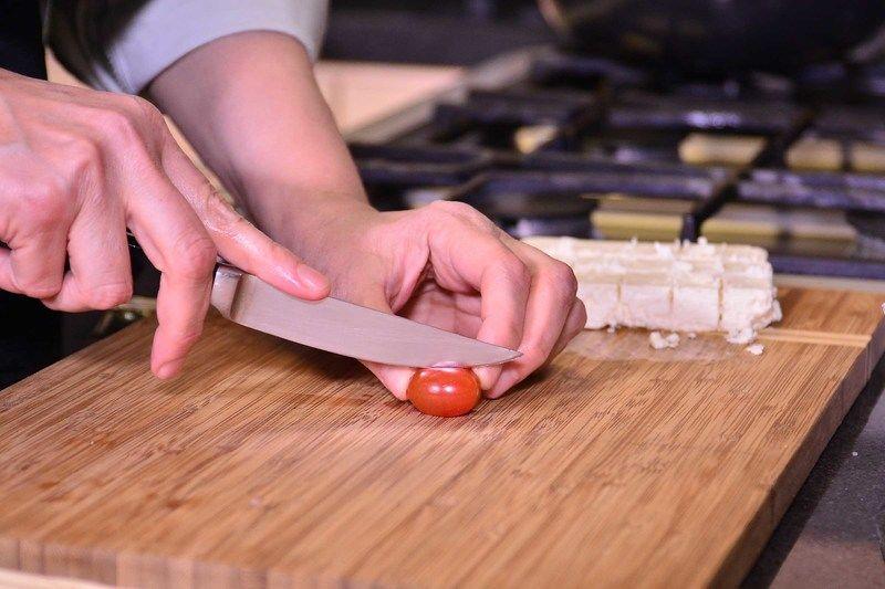 Para preparar los jitomates rostizados, cortar los tomatitos cherry a la mitad.