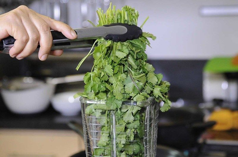 Colocar en el vaso de la licuadora el manojo de cilantro, diente de ajo.