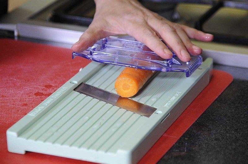 Rebanar la calabacita y la zanahoria en tiras delgadas a lo largo usando una mandolina.