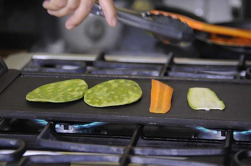 Asar sobre al comal las pencas de nopal, rebanadas de calabacita y zanahoria unos minutos por cada lado.