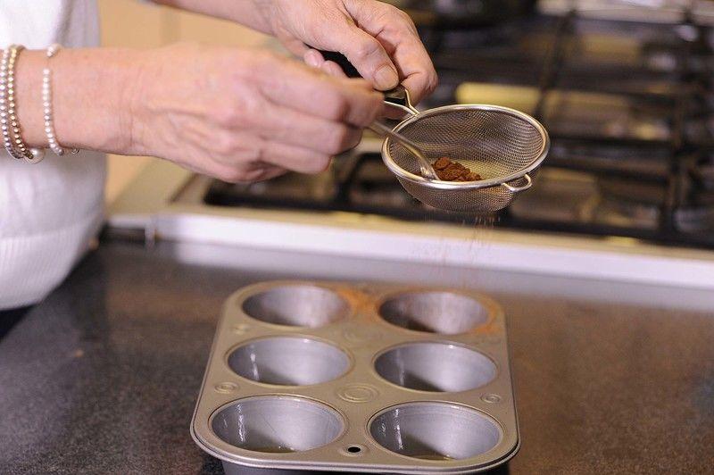 Preparar la charola de cup cakes con mantequilla derretida y cocoa en polvo.