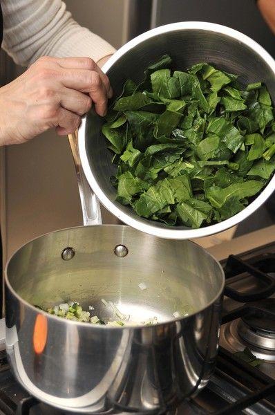 Acitronar la cebolla picada y el chile serrano en una olla honda con aceite de oliva durante un par de minutos. Agregar las espinacas y continuar cociendo de 3 a 5 minutos hasta que se suavicen.