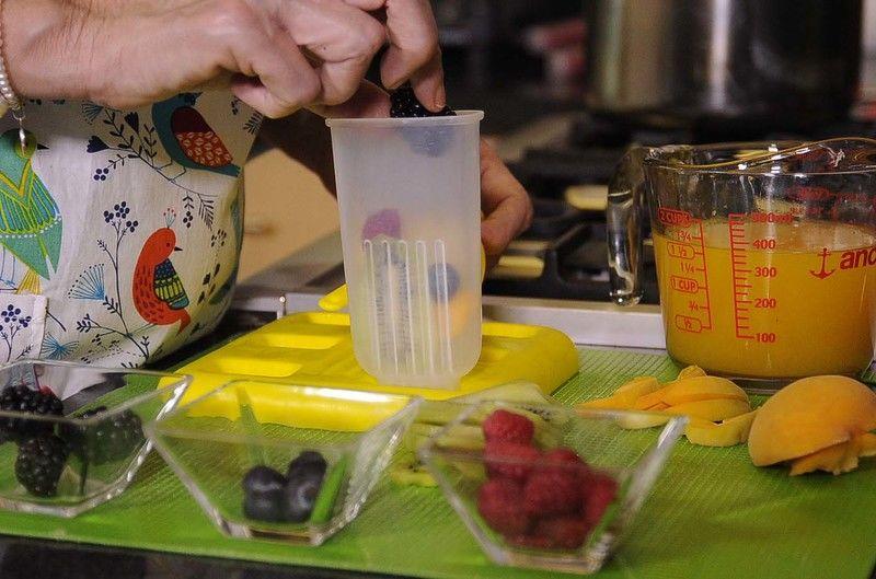 Poner la fruta en los moldes de las paletas.