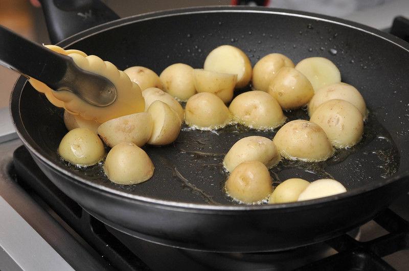 Calentar el aceite en un sartén y acitronar el ajo durante 2 minutos hasta que se ablande. Retirar del fuego. Agregar las papas y revolver bien. Colocar las papas en una fuente para horno. Sazonar con sal al gusto y comino. Hornear a 350°F (175°C) durante 25 a 30 minutos hasta que las papas estén cocidas y doradas.