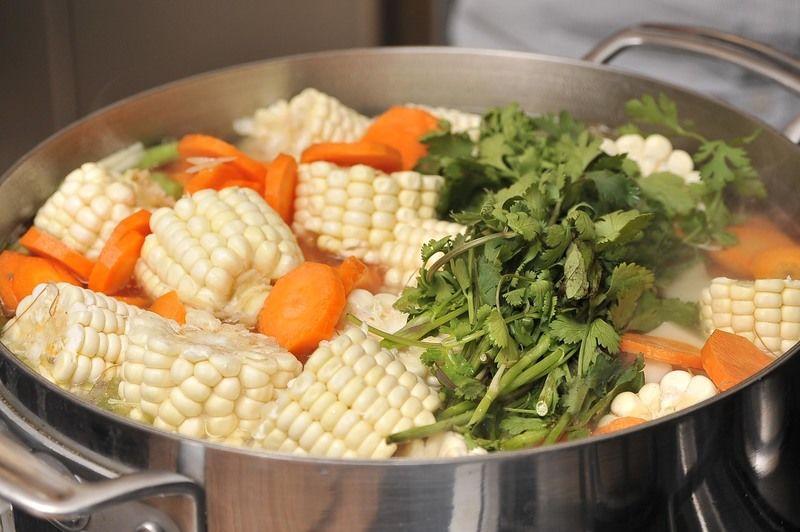 Cortar los elotes en rueditas. Cuando la carne, que puede incluir médula está cocida, agregar col o repollo picado en tiras, papa en trozos, zanahoria en rodajas, ejote en trozoas, apio en rodajas, hierbabuena y cilantro; dejar cocer por 20 0 25 minutos más. Rectificar la sazón.