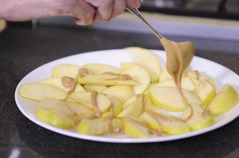 Mezclar la mantequilla de cacahuate y la miel, meter al microondas por 10 seg. para suavizar. Vaciar sobre las manzanas.