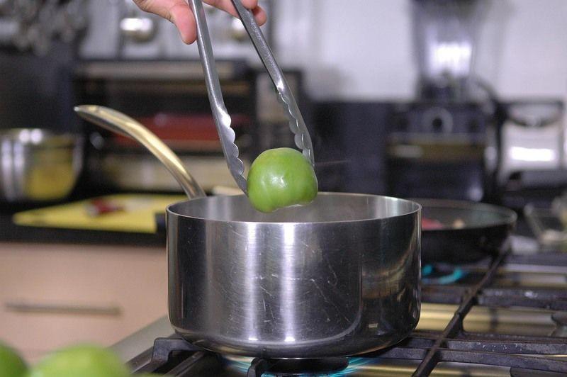 Poner a hervir los tomates verdes junto con los chiles serranos durante cinco minutos hasta que cambien de color pero antes de que se reviente piel. Dejar enfriar un poco.