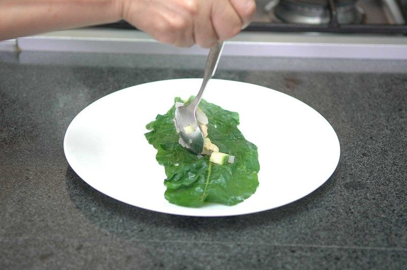 Colocar una hoja de acelga y rellenar con un poco de la mezcla de pollo y enrollar bien para formar una bolita.