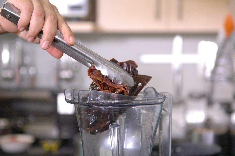 Colocar en el vaso de la licuadora las pieles de los chiles, ajo y jitomate y un poquito del agua donde se cocieron. Moler bien hasta obtener una mezcla homogénea.