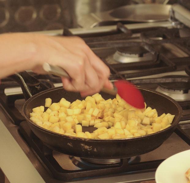 Retirar las pechugas de la sartén, poner a freír la manzana en la misma grasa durante 2 a 3 minutos, moviendo constantemente.