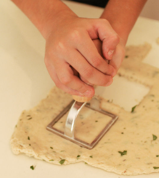 Espolvorear harina sobre la cubierta y extender la masa con el rodillo hasta que tenga aproximadamente 1/2 centímetro de espesor. Cortar en cuadros de 6 centímetros de lado, utilizando un cuchillo o un cortador de galletas cuadrado.