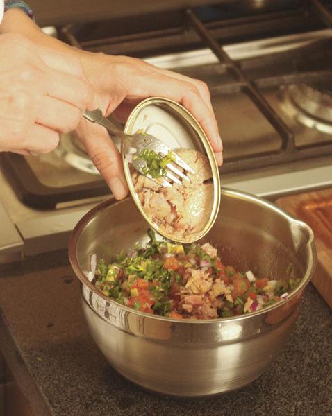 Picar finamente el cilantro, las aceitunas y la cebolla morada. Mezclar en un tazón el atún con el jitomate, cilantro, orégano, aceite de oliva, vinagre, aceitunas y cebolla. Sazonar con sal y pimienta.