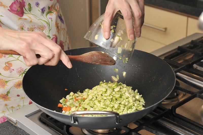 Picar finamente el ajo. Picar finamente la cebolla cambray, colocando por separado la parte blanca y la verde. Pelar las zanahorias, picar finamente al igual que la calabacita. Calentar el aceite y freír el ajo, la zanahoria, la parte blanca de la cebolla y la calabaza durante 3 minutos.