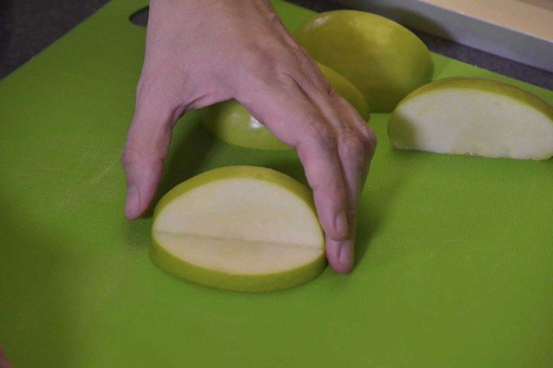 Tomar la mitad de cada manzana y cortar en dos partes. Hacer un corte triangular a cada cuarto de manzana sin cortar totalmente, esto permitirá obtener la figura de una boca.