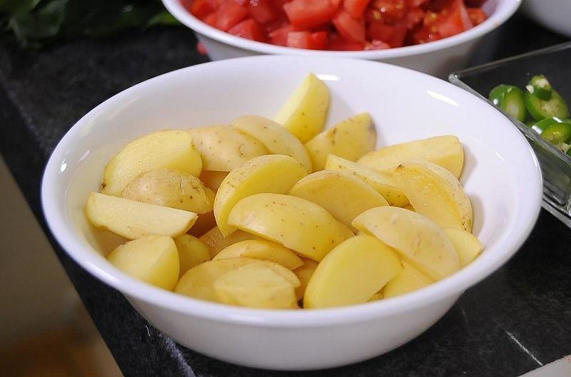 Picar finamente la cebolla, cilantro, el chile serrano en rodajas y el jitomate en cuadros pequeños, y las papas en cuartos. Reservar.