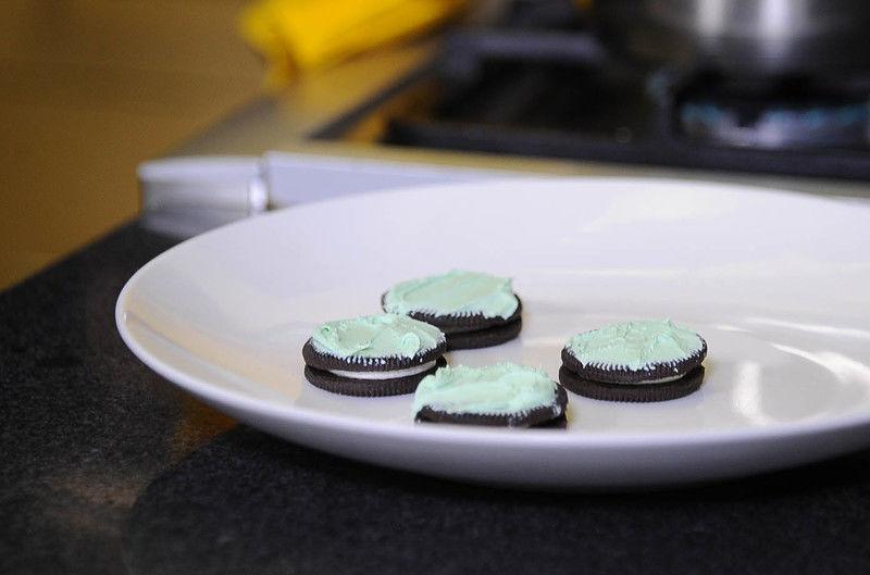 Cuando se derrita bajar la temperatura, agregar el colorante verde hasta obtener el color deseado, untar un poco a cada galleta, servirá para que la fresas se peguen.