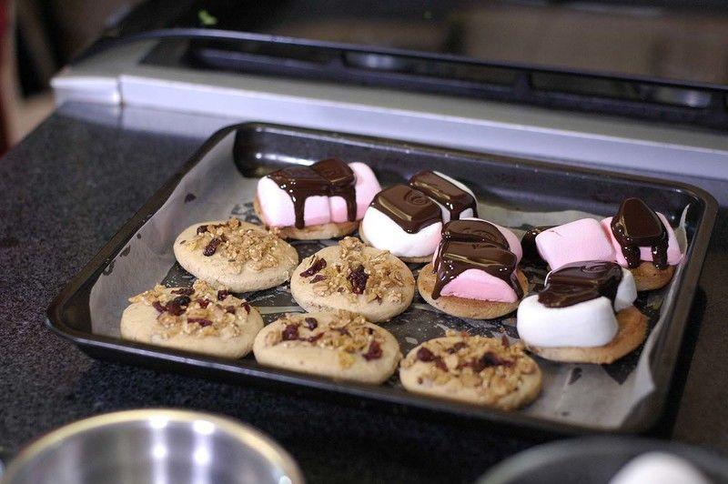 Colocar sobre él un trozo de chocolate y otra galleta encima para formar un sándwich.Presionar con la ayuda de la pala el sándwich y volver a hornear durante 3 minutos más.