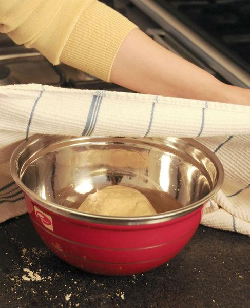 Una vez mezclado golpear la masa sobre la mesa hasta que deje de pegarse, si es necesario espolvorear más harina. Engrasar un tazón con una cucharada de aceite vegetal, colocar ahí la masa, tapar con papel plástico y dejar reposar por una hora.