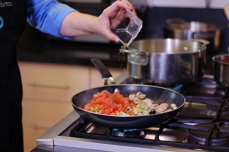 Agregar jitomates, albahaca, orégano, y sazonar con sal y pimienta. Dejar cocinar durante un par de minutos más.