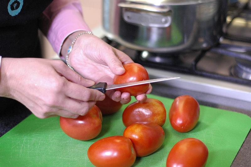 Hacer una incisión en forma de cruz en la base de los jitomates para cortar solamente la piel.