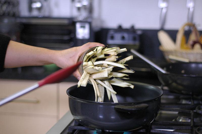 Calentar el aceite y sofreír el ajo picado un par de minutos, agregar la berenjena y continuar cociendo durante 5 minutos o hasta que esté suave.