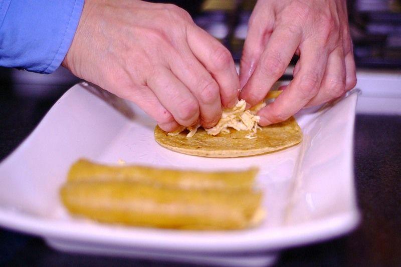 Rellenar cada tortilla con un poco de pollo deshebrado y colocar en un platón hasta terminar de rellenar todas.