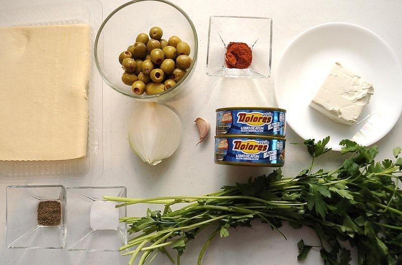 Ingredientes para receta 1/4 pieza de cebolla blanca 1 pieza de diente de ajo 2 latas de atún en aceite 1 cucharita de paprika 1 taza de aceituna rellena pimienta negra molida al gusto sal al gusto 400 gramos de pasta de hojaldre 95 gramos de queso crema 1/4 manojo de perejil