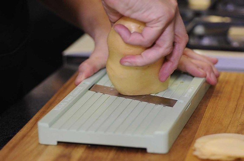 Colocar sobre la tabla de picar la mandolina y rebanar la papa en rebanadas delgadas hasta terminar con todas.