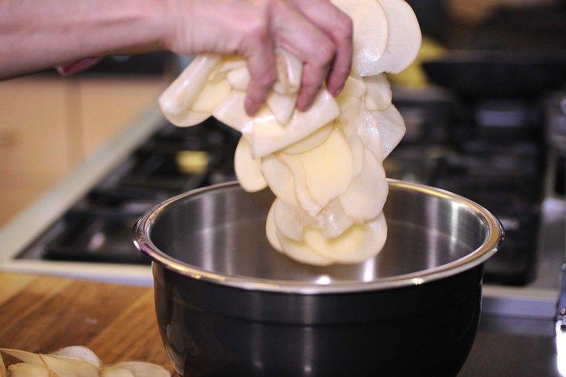 Añadir las rodajas de papa en un tazón, sal de grano, la pimienta, la paprika.