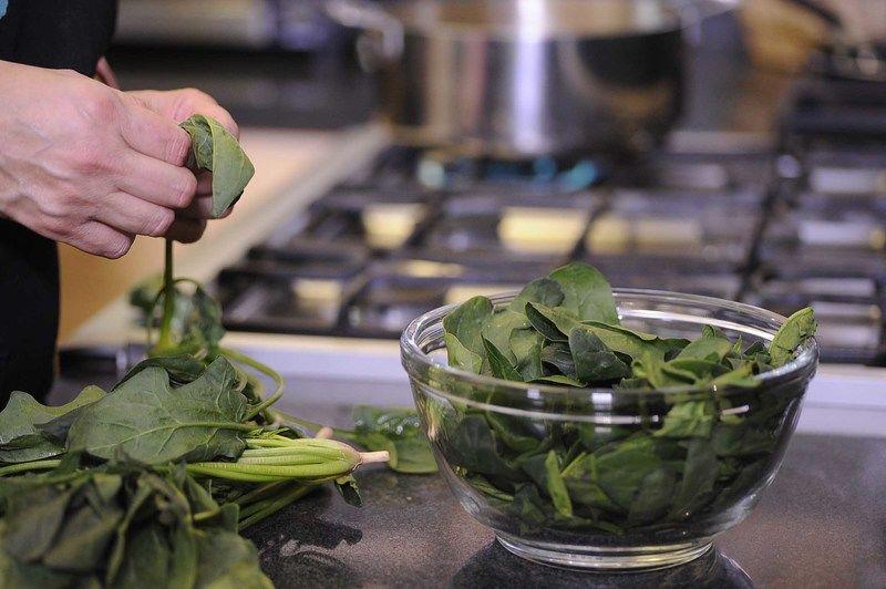 Retirar las hojas de espinaca del tallo y enjuagar con suficiente agua y reservar. Picar el diente de ajo finamente.