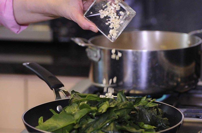 Calentar el sartén y cuando este caliente añadir las hojas de espinaca, ajo y dejar cocer un par de minutos para que se suavicen.