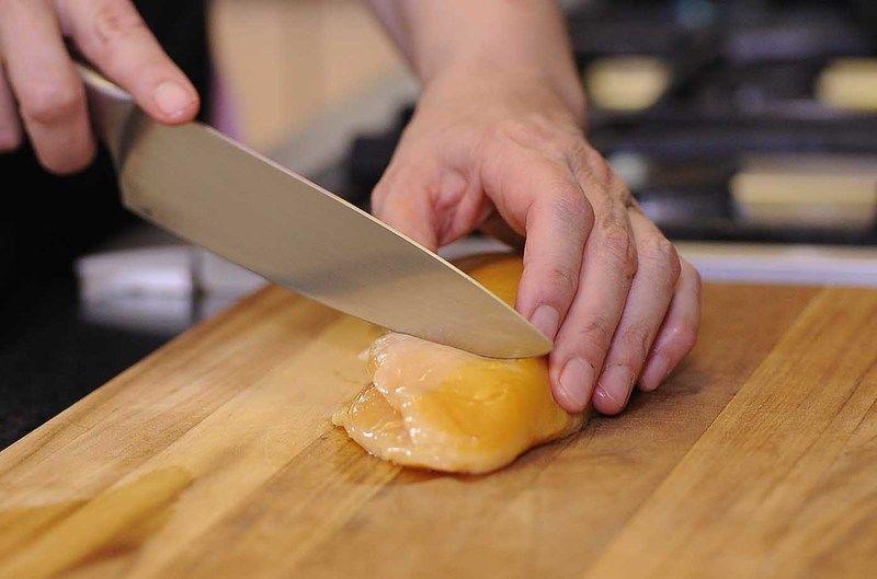 Colocar la media pechuga de pollo sobre la tabla para picar y hacer cortes en diagonal cuidando de no cortar totalmente la carne.