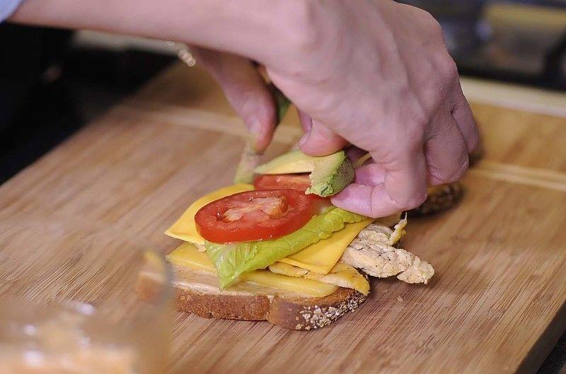 Colocar una rebanada de queso manchego, unas tiras de pollo, una rebanada de queso amarillo, una hoja de lechuga, rebanada de jitomate, rebanadas de aguacate.